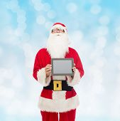 christmas, advertisement, technology, and people concept - man in costume of santa claus with tablet pc computer over blue lights background