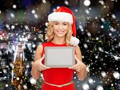 christmas, technology, present and people concept - smiling woman in santa helper hat with tablet pc computer showing blank screen over snowy night city background