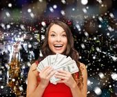 christmas, sale, banking, winning and holidays concept - smiling woman in red dress with us dollar money over snowy night city background