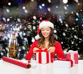 christmas, holidays, celebration, decoration and people concept - smiling woman in santa helper hat with decorating paper packing gift boxes over snowy night city background