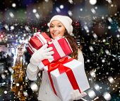 happiness, winter holidays, christmas and people concept - smiling young woman in santa helper hat with gifts over snowy night city background