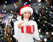 christmas, winter, happiness, holidays and people concept - smiling woman in santa helper hat with gift box over snowy night city background