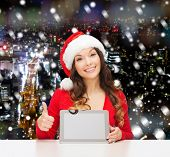 christmas, holidays, technology and people concept - smiling woman in santa helper hat with tablet pc computer showing thumbs up over snowy night city background