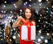 christmas, holidays, valentine's day, celebration and people concept - smiling woman in red dress with gift box over snowy night city background