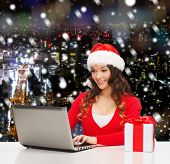 christmas, holidays, technology and people concept - smiling woman in santa helper hat with gift box and laptop computer over snowy night city background