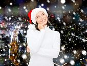 christmas, holidays, winter, happiness and people concept - thinking and smiling woman in santa helper hat over snowy night city background