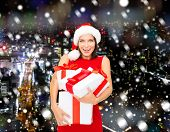christmas, winter, happiness, holidays and people concept- smiling woman in santa helper hat with gift boxes over snowy night city background