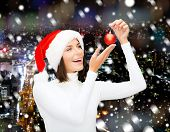 winter, people, christmas and happiness concept - woman in santa helper hat with christmas tree decoration ball over snowy night city background