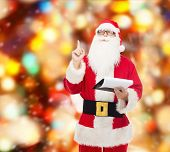 christmas, holidays, gesture and people concept - man in costume of santa claus with notepad pointing finger up over red lights background