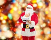 christmas, holidays and people concept - man in costume of santa claus with notepad over red lights background