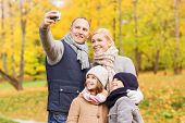 family, childhood, season, technology and people concept - happy family taking selfie with camera in autumn park