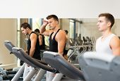 sport, fitness, lifestyle, technology and people concept - group of men exercising on treadmill in gym
