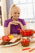 Attractive young female preparing cheese fondue at home, smiling, looking at camera.