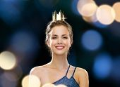 people, holidays, royalty, celebration and glamour concept - smiling woman in evening dress wearing golden crown over black background over night lights background