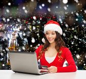 christmas, holidays, technology and shopping concept - smiling woman in santa helper hat with credit card and laptop computer over snowy night city background