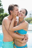 Young man kissing woman by swimming pool on a sunny day