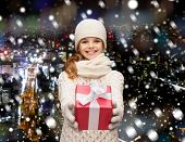 christmas, holidays, childhood, presents and people concept - dreaming girl in winter clothes with gift box over snowy city background