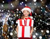 holidays, presents, christmas, childhood and people concept - smiling little girl in santa helper hat with gift boxes over snowy night city background