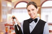 Portrait of a smiling female waiter holding a champagne bottle. Isolated on white