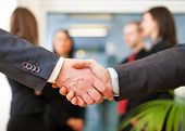 Business people shaking their hands in an office