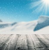 Snowy winter landscape with empty wooden planks