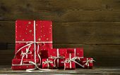 Red christmas presents on an old wooden brown background.