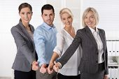Successful business team in portrait: more woman as men with thumbs up.