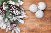 Christmas fir tree with snow and baubles on rustic wooden board with copy space