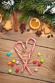 Christmas wooden background with snow fir tree, spices and gingerbread cookies