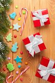 Christmas wooden background with snow fir tree, gingerbread cookies and gift boxes
