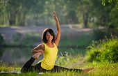 Woman Performs Yoga Exercises And Pilates In Nature