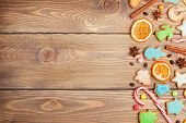 Christmas wooden background with candies, spices, gingerbread cookies and copy space