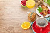 Healthy breakfast with muesli, berries, orange juice, coffee and croissant. On wooden table with copy space