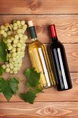 Red and white wine bottles and bunch of grapes on wooden table