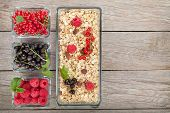 Healthy breakfast with muesli and berries. View from above on wooden table with copy space