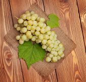 Bunch of white grapes on wooden table background