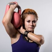 Portrait Close Up Of Young Attractive Female Doing Kettle Bell Exercise On Grey Background