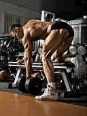 foto of execution  - very power athletic guy execute exercise with dumbbells on bkack background - JPG