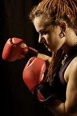 Beautiful Woman With Red Boxing Gloves, Dreadlocks On A Black Background.
