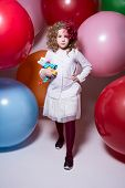 Beautiful Girl In A White Blouse With A Soft Toy Comes At Camera On Background Of Large Balloons.