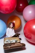 Girl Schoolgirl With Wooden Abacus And Lying In A Suitcase With Dollars.