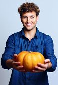 Portrait of a happy man holding pumpkin over blue background