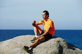 Relaxed fit man listening to music sitting on sea rocks outdoors