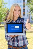 Beautiful Woman Holding Laptop With Login Panel On Screen And Thumbs Up In Park