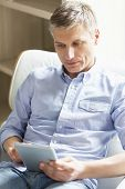 Middle-aged man using digital tablet at home