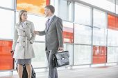 Businessman and businesswoman talking while walking on railroad platform