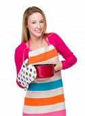 Housewife with saucepan and heat insulation gloves