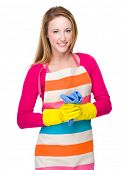 Housewife with kitchen gloves and hold towel