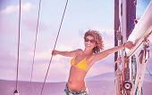 Happy smiling female standing on the deck of yacht with raised up hands, active summer adventure, enjoyment and happiness concept