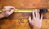 Male hand measuring wooden floor